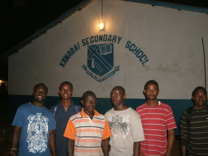 Idrissa and Jalloh outside a school in 2011, with the principle, a student and other EFO members.